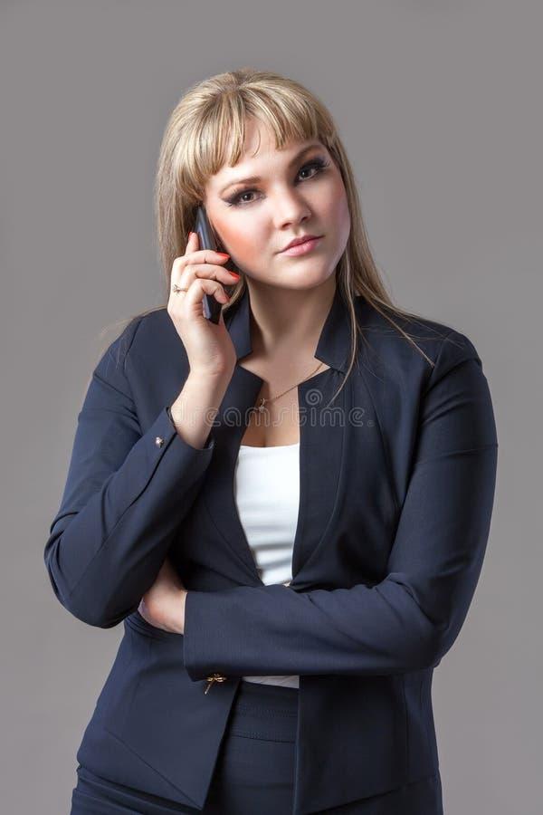 Geschäftsfrau in der blauen Klage sprechend am Telefon stockbilder
