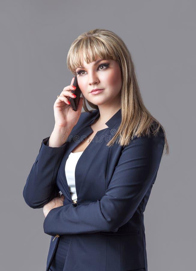 Geschäftsfrau in der Klage sprechend an einem Handy stockfotografie
