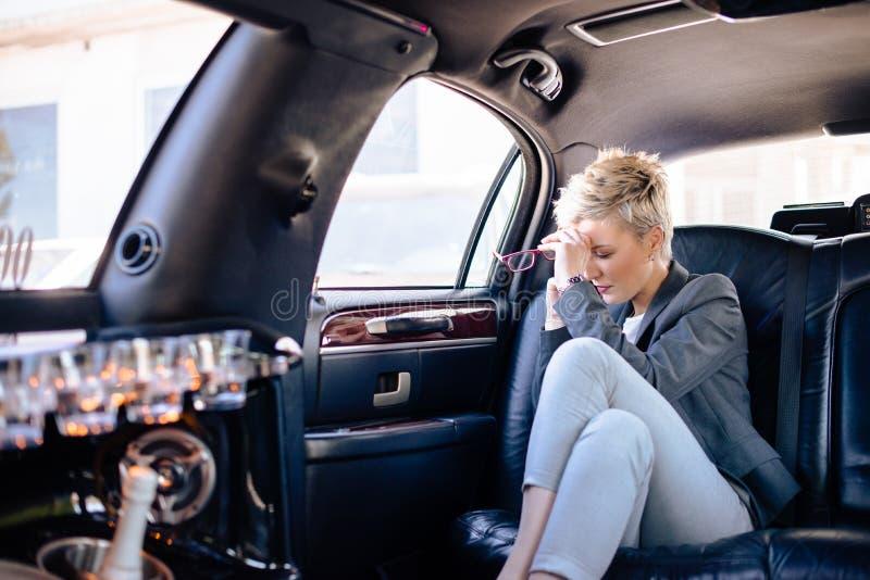 Geschäftsfrau an der Limousine, die stressigen Tag hat stockfoto