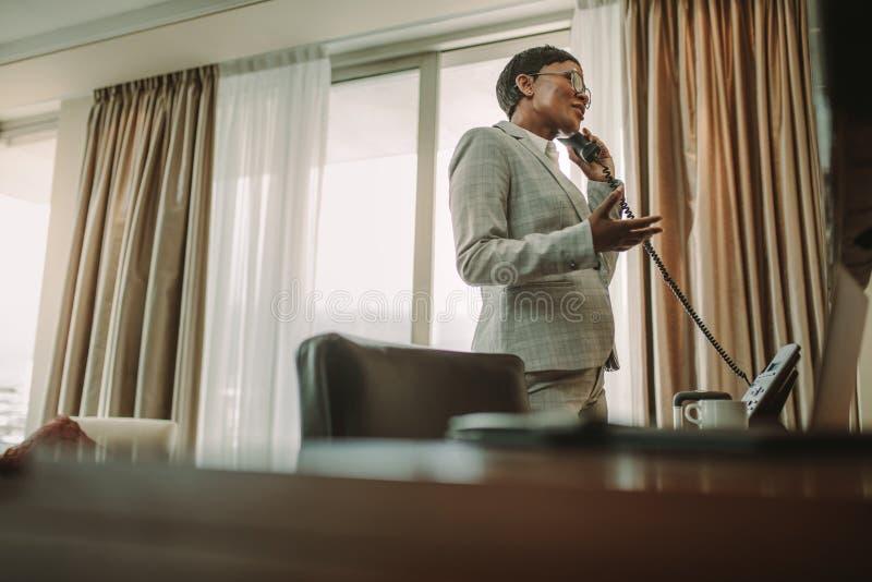 Geschäftsfrau, die über Überlandleitungstelefon vom Hotelzimmer spricht stockfotografie