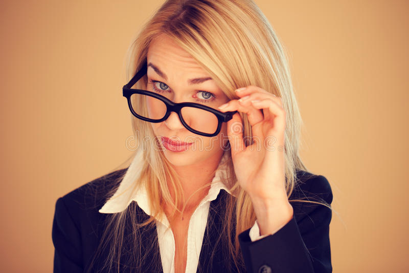 Geschäftsfrau, die über ihren Gläsern blickt stockbild