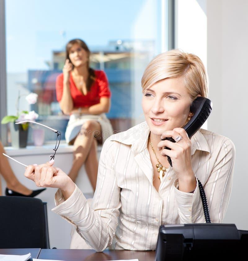Geschäftsfrau, die am Überlandleitungtelefon spricht stockfotos