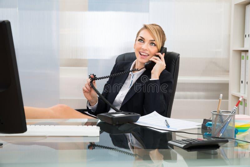 Geschäftsfrau, die am Überlandleitungtelefon spricht lizenzfreies stockbild