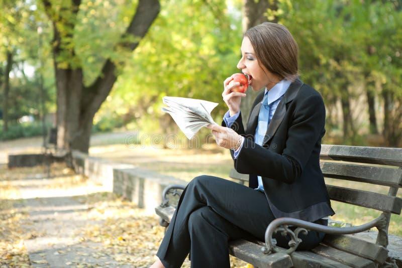 Geschäftsfrau, die Apfel isst lizenzfreie stockfotografie