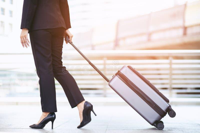 Geschäftsfrau, die außerhalb des Gebäudes der öffentlichen Transportmittel mit Gepäck in der Hauptverkehrszeit geht Geschäftsreis lizenzfreie stockfotos