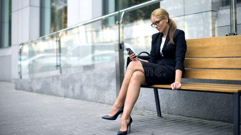 Geschäftsfrau, die auf Bank sitzt und das Telefon, stehend in der Freizeit, Bruch verwendet still lizenzfreie stockfotos