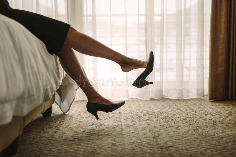 Geschäftsfrau, die auf Bett nach einer langen Tagesarbeit sich entspannt stockfotografie