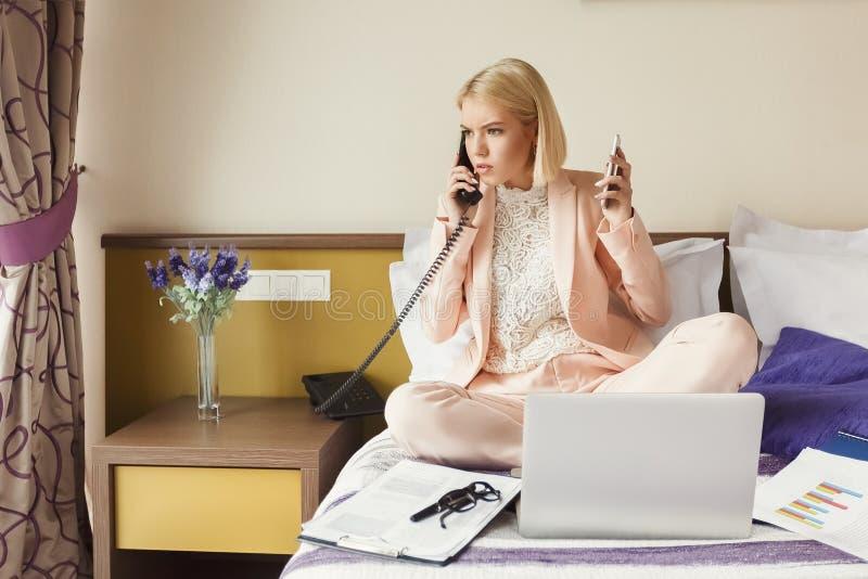 Geschäftsfrau, die auf Bett sitzt und Laptop verwendet lizenzfreies stockbild