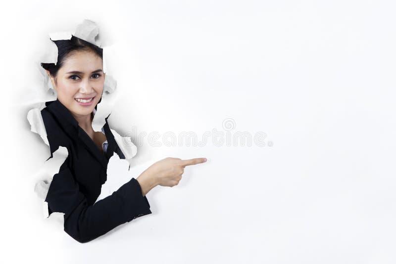 Geschäftsfrau, die auf copyspace auf Papierwand zeigt lizenzfreie stockfotografie