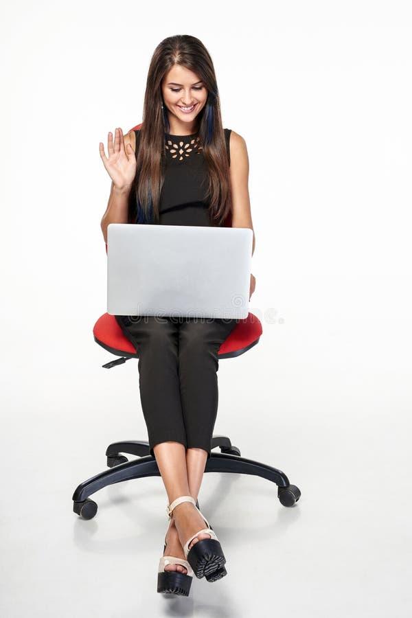 Geschäftsfrau, die auf dem Bürostuhl arbeitet mit Laptop sitzt lizenzfreies stockfoto