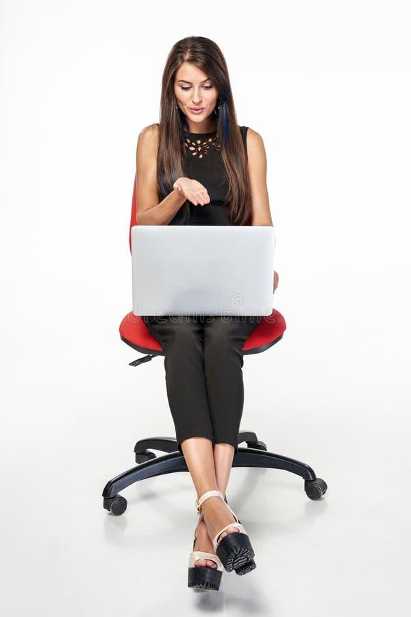 Geschäftsfrau, die auf dem Bürostuhl arbeitet mit Laptop sitzt stockfotos