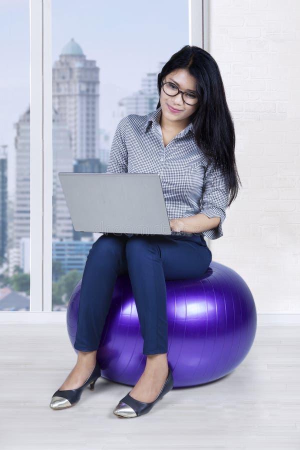 Geschäftsfrau, die auf dem Ball sitzt lizenzfreies stockfoto