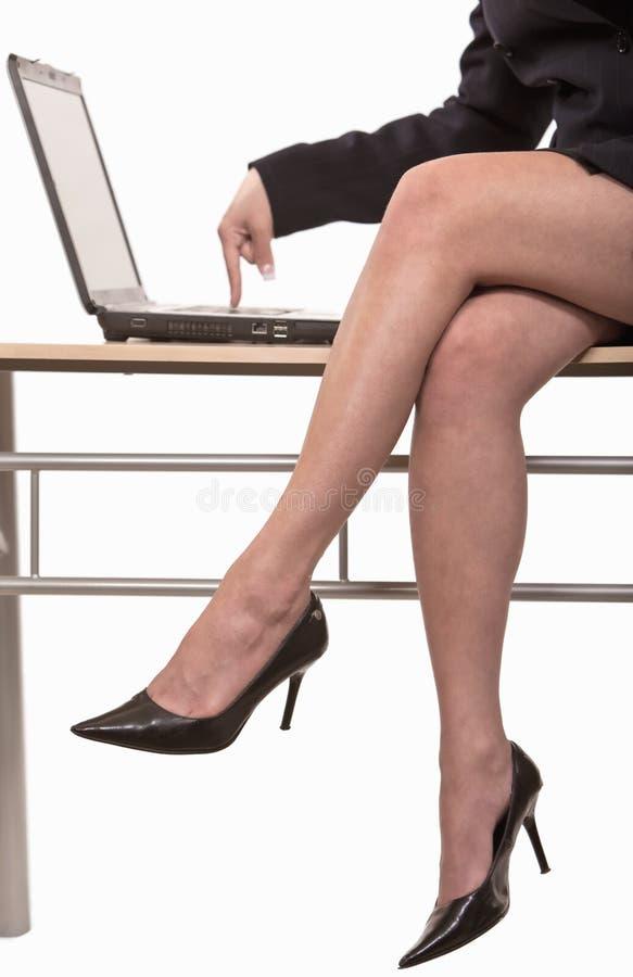 Geschäftsfrau, die auf der Tabelle schreibt auf Laptop sitzt lizenzfreie stockbilder