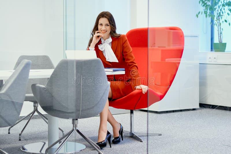 Geschäftsfrau, die auf einem roten Stuhl in einem Glasbüro lächelt und sitzt lizenzfreie stockfotos
