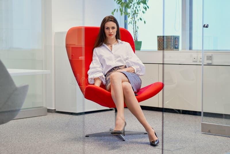 Geschäftsfrau, die auf einem roten Stuhl in einem Glasbüro sitzt lizenzfreie stockbilder