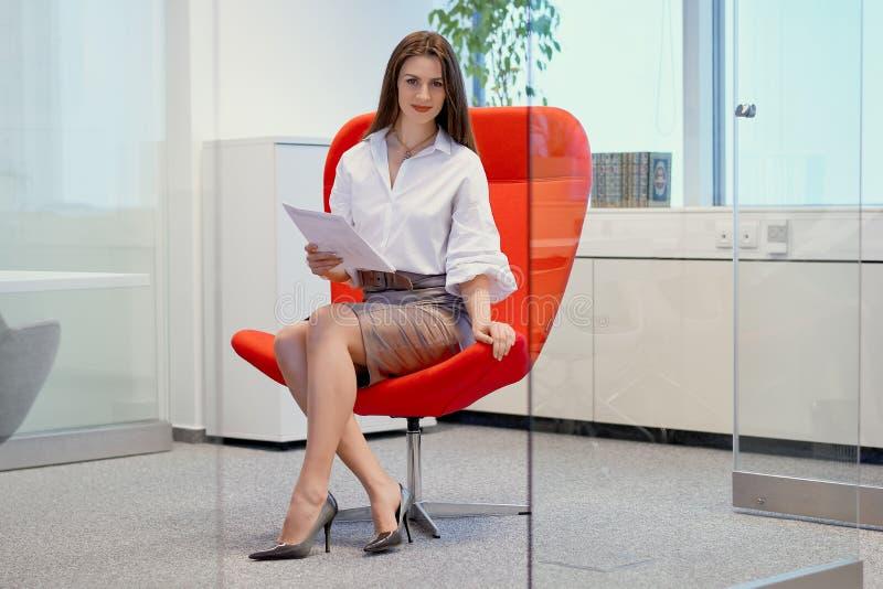 Geschäftsfrau, die auf einem roten Stuhl in einem Glasbüro und in den Kontrolldokumenten sitzt stockbilder