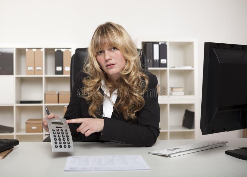 Geschäftsfrau, die auf einen Taschenrechner zeigt stockfotos
