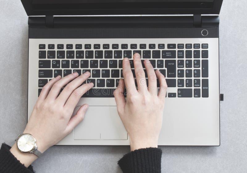 Geschäftsfrau, die auf einer Laptoptastatur auf grauem Hintergrund schreibt stockfotos