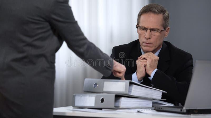 Geschäftsfrau, die auf Fälle mit Mehrarbeit, hohe Nachfragen zum Assistenten zeigt stockfotos