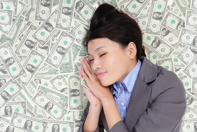 Geschäftsfrau, die auf Geldbett schläft stockbilder