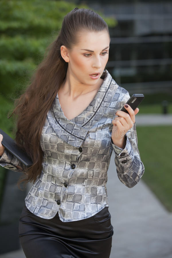 Geschäftsfrau, die auf Handy überrascht schaut lizenzfreie stockbilder