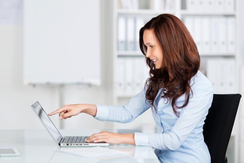 Geschäftsfrau, die auf ihren Laptop zeigt stockfoto