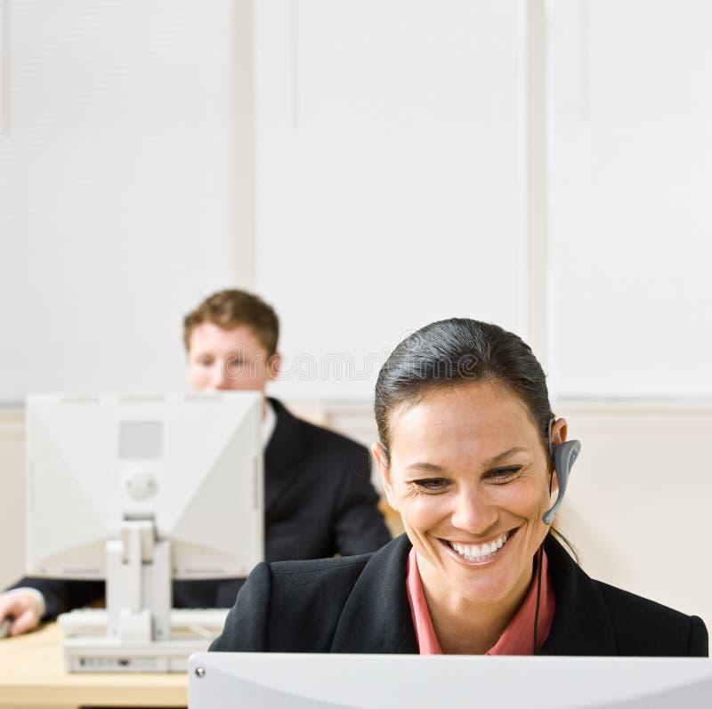 Geschäftsfrau, die auf Kopfhörer spricht lizenzfreies stockfoto