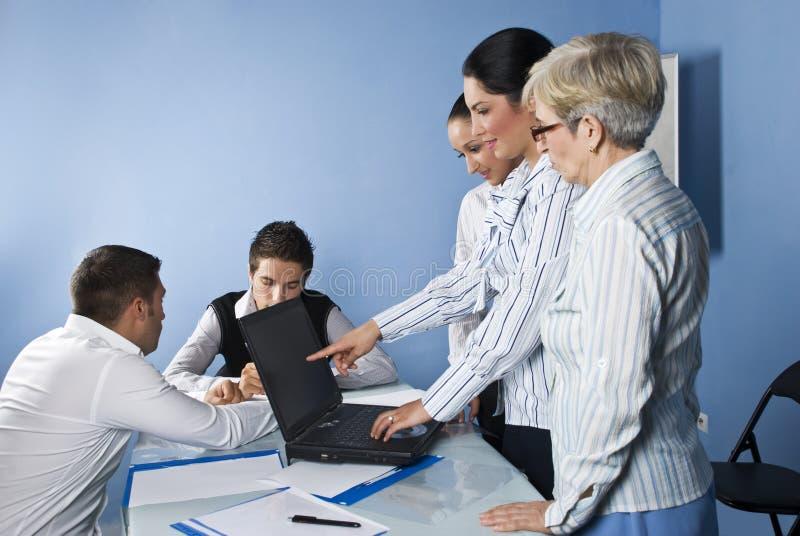 Geschäftsfrau, die auf Laptop bei der Sitzung zeigt lizenzfreie stockbilder