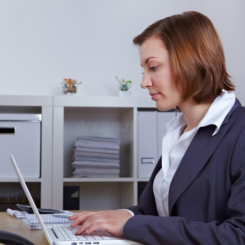 Geschäftsfrau, die auf Laptop-Computer schreibt stockfoto