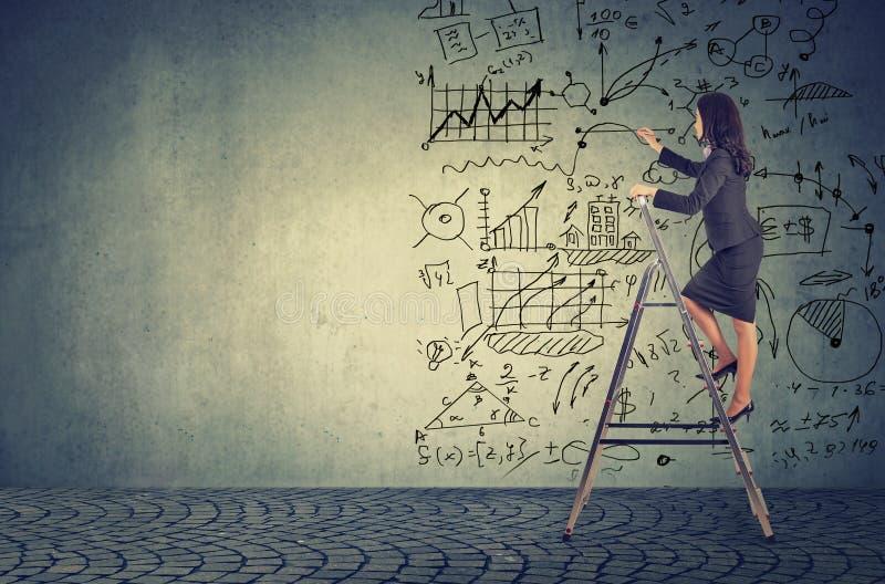 Geschäftsfrau, die auf Leiter und zeichnenden Unternehmensplanideen steht lizenzfreies stockbild