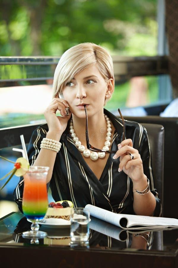 Geschäftsfrau, die auf Mobile im Kaffee spricht stockbilder