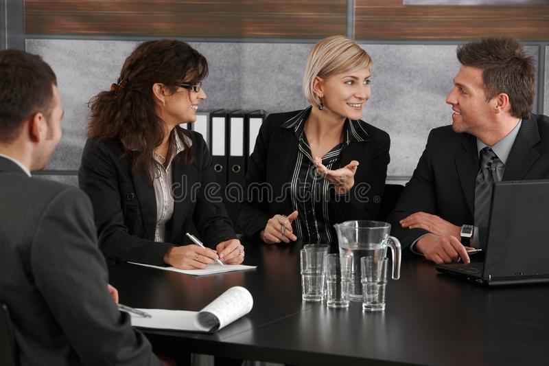 Geschäftsfrau, die auf Sitzung erklärt stockfotografie
