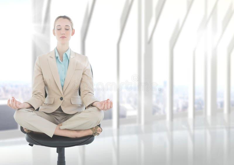 Geschäftsfrau, die auf Stuhl mit Aufflackern gegen undeutliches weißes Fenster meditiert stockfotos