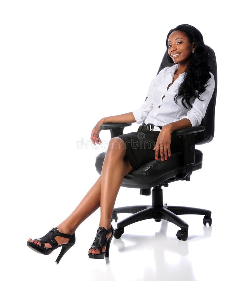 Geschäftsfrau, die auf Stuhl sitzt stockbild