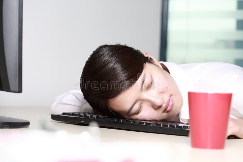 Geschäftsfrau, die auf Tastatur schläft stockfotos