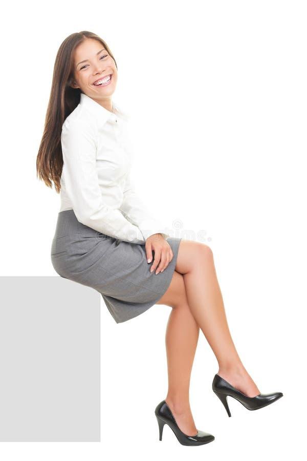 Geschäftsfrau, die auf unbelegtem Zeichen sitzt lizenzfreie stockfotografie