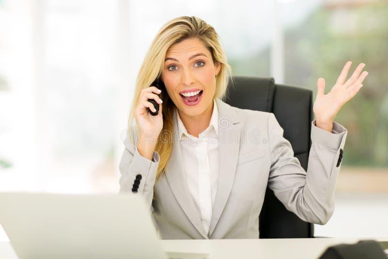 Geschäftsfrau, die aufregende Nachrichten empfängt stockfotografie