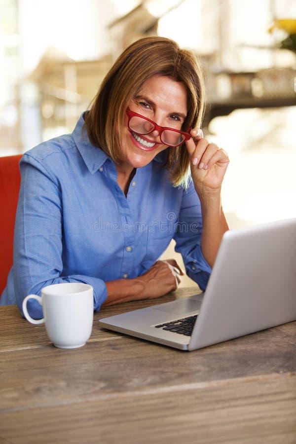 Geschäftsfrau, die bei Tisch lächelt und mit Laptop-Computer arbeitet lizenzfreies stockfoto