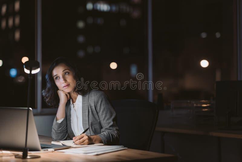 Geschäftsfrau, die beim Arbeits Überstunden ihrem Schreibtisch gebohrt betrachtet stockbilder