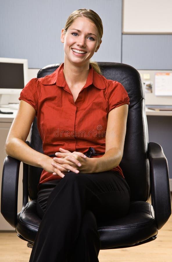 Geschäftsfrau, die beim Stuhllächeln sitzt stockbilder