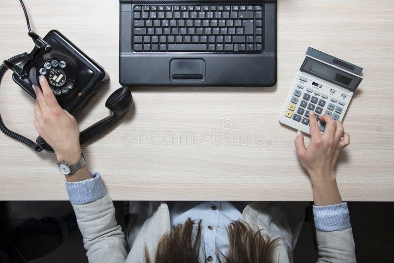 Geschäftsfrau, die Berechnungen tut und eine Telefonnummer wählt stockfotografie