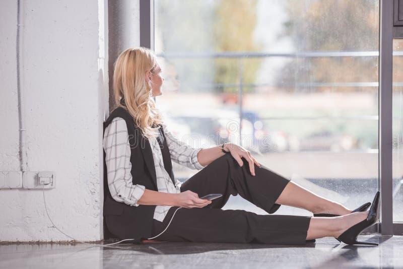 Geschäftsfrau, die am Boden und an Aufladungstelefon sitzt lizenzfreie stockfotografie