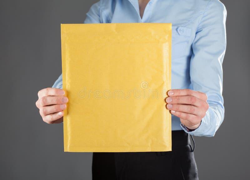 Geschäftsfrau, die Buchstaben im gelben Umschlag zeigt stockbilder