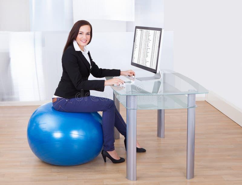 Geschäftsfrau, die Computer beim Sitzen auf pilates Ball verwendet stockfotografie