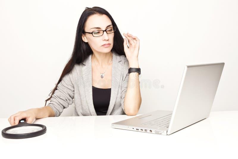 Geschäftsfrau, die Computer unter Verwendung der Lupe überprüft stockfoto