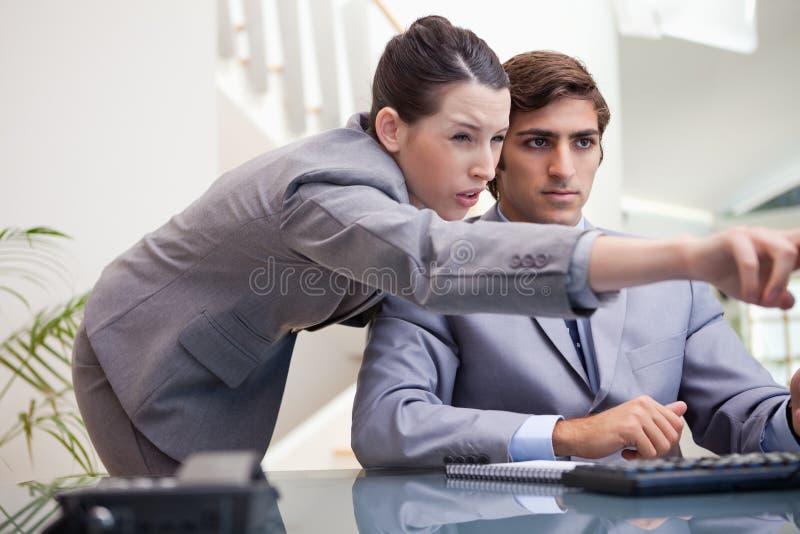 Geschäftsfrau, die Computerprogramm erklärt stockfotos