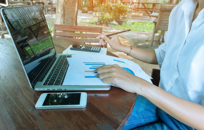 Geschäftsfrau, die das Diagrammdokument finanziell mit Laptop- und Handyweinleseton analysiert stockbilder