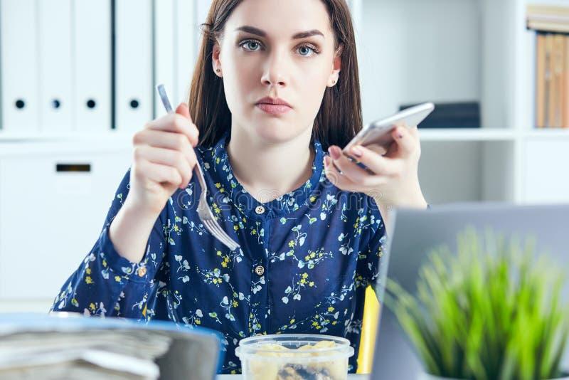 Geschäftsfrau, die das Mittagessen an ihrem Arbeitsplatz betrachtet den Laptopschirm isst Ordner mit Dokumenten im Vordergrund stockfotos