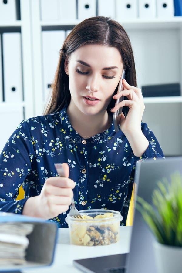 Geschäftsfrau, die das Mittagessen an ihrem Arbeitsplatz betrachtet den Laptopschirm isst Ordner mit Dokumenten im Vordergrund stockbilder