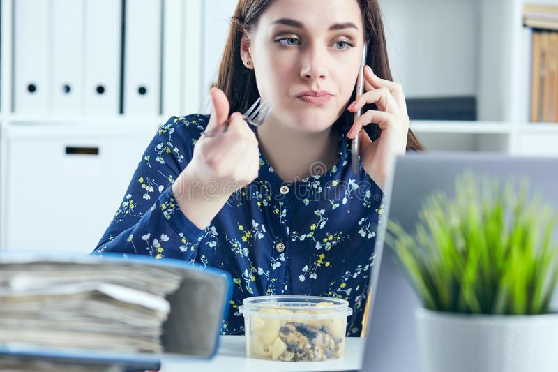 Geschäftsfrau, die das Mittagessen an ihrem Arbeitsplatz betrachtet den Laptopschirm isst Ordner mit Dokumenten im Vordergrund lizenzfreie stockfotografie